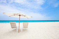 Two chairs under umbrella at beach Stock Images