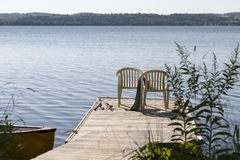 Two chairs on a wooden deck with fishing rods. Two chairs on a wooden deck by the lake with fishing rods Stock Photography