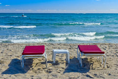 Two chaise longue on the beach. Two red chaise longue and a table on the beach royalty free stock photography