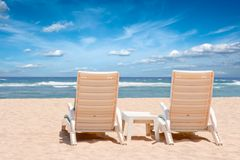 Two chaise longues on beach near ocean Stock Images