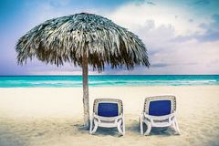 Two chaise lounges on the beach. Two chaise lounges and an umbrella on the beach Stock Photos