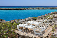 Two chaise-lounges on the coral beach. Of the Caribbean sea stock photography