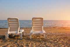Two chaise lounges on sand on seashore, rear view. Background of sky and the sea in the evening stock images