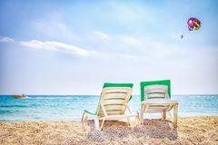 Two chaise lounges on sea beach. Sun beds on sea. Parasailing with boat over sea. Relax vacation on tropical resort beach.  Stock Image