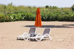 Two chaise lounges stand on the sand with a closed umbrella royalty free stock image