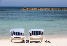 Two Chaise Lounges with Towels on Beach. Two chaise lounges on a Caribbean beach with blue towels royalty free stock images