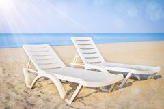 Two chaise lounges on tropical beach resort. Concept vacation. B. Each, sand and sea Stock Photo
