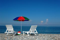 Two chaise lounges and umbrella on a beach Stock Photos