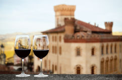 Two chalices of wine with the castle of Barolo Italy stock photography
