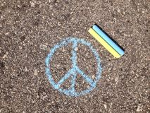 Two chalk on asphalt. Yellow and blue colors of the two pieces of chalk royalty free stock photos