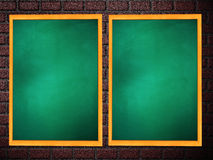 Two chalkboards of green color on brick wall Stock Image