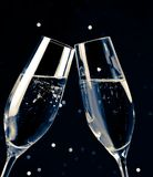 Two champagne flutes on black dark light bokeh background Royalty Free Stock Photography
