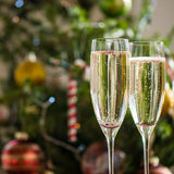 Two Champagne Flutes on Christmas Background Stock Photos