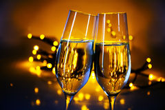 Two champagne flutes clink glasses at Christmas or New Year's  p. Arty, warm golden background with blurred lights and copy space Royalty Free Stock Images