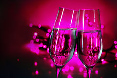 Two champagne flutes clink glasses on New Year's party, purple b Stock Photo