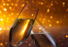 Two champagne flutes with gold bubbles on dark light bokeh background. Two champagne flutes with gold bubbles make cheers on dark light bokeh background Stock Image