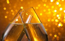 Two champagne flutes with gold bubbles on dark light bokeh background. Two champagne flutes with gold bubbles make cheers on dark light bokeh background with Stock Photography