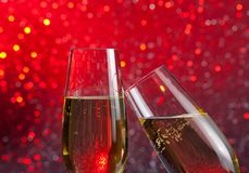 Two champagne flutes with gold bubbles on red light bokeh background Stock Photos