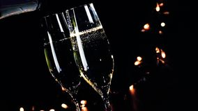 Two champagne flutes with golden bubbles on black dark light background, new year atmosphere stock video