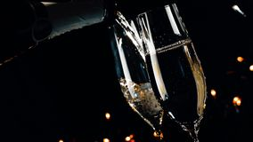 Two champagne flutes with golden bubbles on black dark light background, new year atmosphere stock footage
