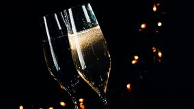 Two champagne flutes with golden bubbles on black dark light background, new year atmosphere stock video footage