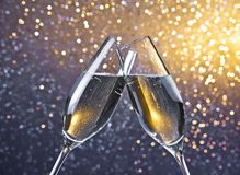 Two champagne flutes with golden bubbles on light bokeh background. Two champagne flutes with golden bubbles make cheers on light bokeh background with space for Stock Image