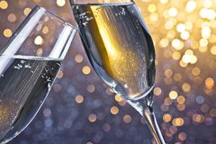 Two champagne flutes with golden bubbles on light bokeh background Royalty Free Stock Photos