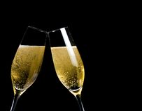 Two champagne flutes with golden bubbles make cheers on black background