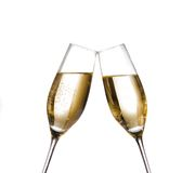 Two champagne flutes with golden bubbles make cheers on white background