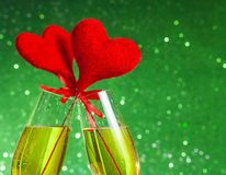 Two champagne flutes with golden bubbles and red velvet hearts make cheers on green bokeh background Royalty Free Stock Photos