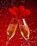Two champagne flutes with golden bubbles and red velvet hearts make cheers on red bokeh background Stock Photos