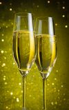 Two champagne flutes with golden bubbles Royalty Free Stock Photography