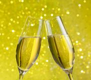 Two champagne flutes with golden bubbles on yellow light bokeh background Stock Images
