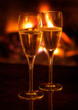 Two champagne flutes lit by log fire. Soft focus Royalty Free Stock Photos