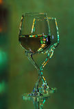 Two champagne flutes on mirror. Flutes on mirror, absinth theme, green lights Stock Photography