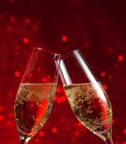 Two champagne flutes on red light bokeh background. Two champagne flutes make cheers on red light bokeh background royalty free stock image
