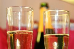 Two champagne glasses. With bottle on background Stock Images