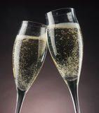 Two champagne glasses against bright lights. Two champagne glasses flute toasting bright lights New Year's Eve Stock Photos