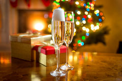 Two champagne glasses against fireplace decorated for Christmas Royalty Free Stock Images