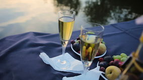 Two champagne glasses against a lake. HD stock video footage