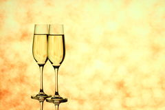 Two champagne glasses on blurred golden background Stock Images