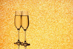 Two champagne glasses on blurred golden background Royalty Free Stock Photography