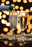 Two champagne glasses with bubbles and bokeh lights in the back Royalty Free Stock Photography