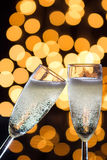 Two champagne glasses with bubbles and bokeh lights in the back Stock Photo