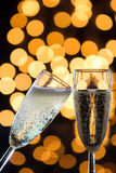 Two champagne glasses with bubbles and bokeh lights in the back Royalty Free Stock Image