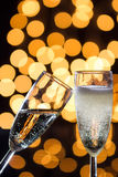 Two champagne glasses with bubbles and bokeh lights in the back Stock Images