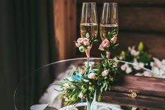 Two champagne glasses decorated with small boutonniere. Two newlyweds glasses with champagne decorated with small boutonniere Stock Photos