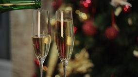 Two Champagne Glasses On Defocused Background Living Room With Christmas Tree. Girl pours champagne in glasses on the background of the Christmas tree stock footage