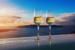 Two champagne glasses on the edge of infinity swimming pool at sunset on Santorini island Royalty Free Stock Photography