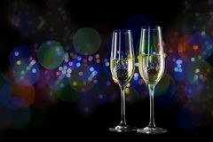 two champagne glasses in front of a dark background with colorful blurred bokeh lights, new year and party concept with copy space royalty free stock image